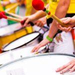 gros plan sur peau de batucada et main des musiciens